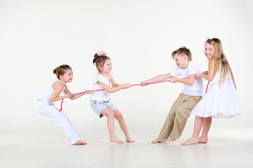 Four happy little boy and girls in white clothes draw over rope