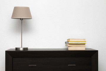 brown commode with lamp and books in bright minimalism interior