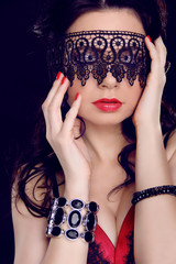 Sexy beautiful woman with black lace pattern on eyes and red lip