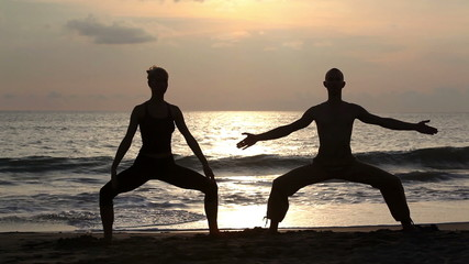 Wall Mural - Couple doing exercise yoga on beach while sunset