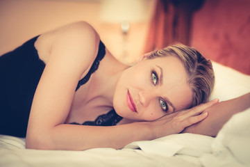 Portrait of a Beautiful Girl Relaxing on Bed in a Hotel Room