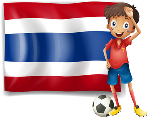 A football player in front of the Thailand flag