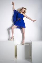 Junge hübsche Frau in Fashion Pose auf Würfel