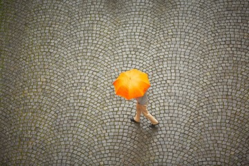 Man with orange umbrella in rain.