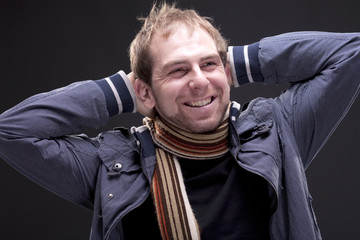 Portrait of young smiling man with a jacket and scarf