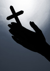 Female hands with crucifix, on bright grey background