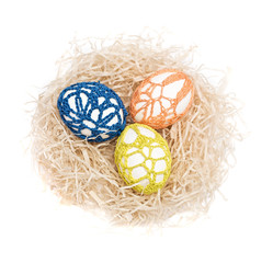 Easter eggs in a nest. Yellow, blue, orange ornament