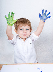 Cute little boy of three years having fun painting