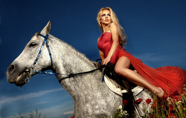 Fashionable blonde woman riding a horse in sunny day