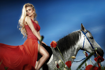 Beautiful blonde woman sitting on a horse in red dress.