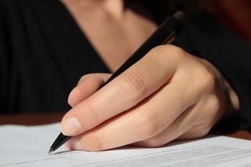 Linke Hand einer Frau unterschreibt einen Vertrag
