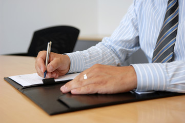 Close-Up Of Writing Hands In Business Environment