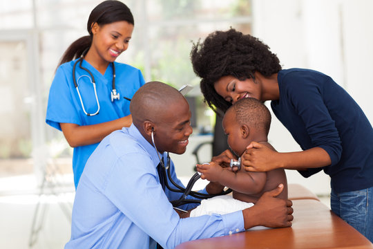 african mother and her son in doctor's office with doctor and nu