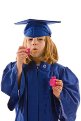 Young graduate in cap and gown blowing bubbles