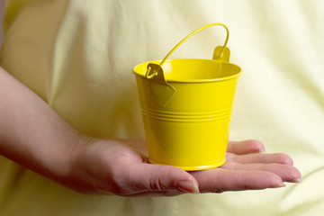 girl holding a small yellow bucket