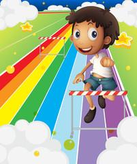 Poster Regenboog A little boy near the stripe hurdle
