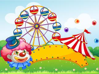 A clown in front of a ferris wheel
