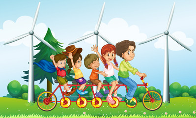 Five kids riding at the bike near the windmills