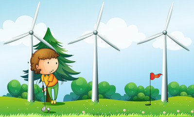 A girl playing golf near the windmills