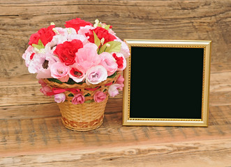 gold picture frame with paper flowers on wooden background