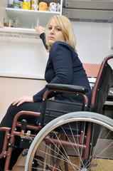 Junge Frau im Rollstuhl hat Mühe im Haushalt