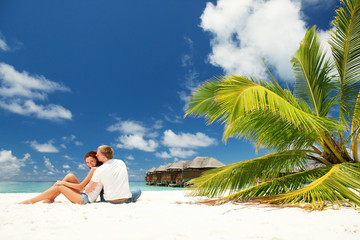 happy couple kissing in the sunny beach