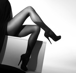 Beautiful legs in nice pantyhose on a grey background