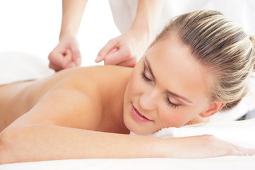 Portrait of a blond woman relaxing on a back massage procedure
