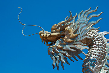 the top half silver dragon statue on blue sky