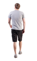 Back view of walking handsome man in shorts and sneakers