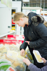 Young mother with daughter select cheese in fridge in supermarke