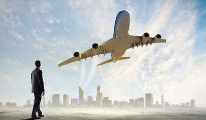 Businessman looking at airplane in sky