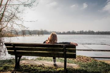 Petite fille sur un banc au bord d'un étang dans les Dombes