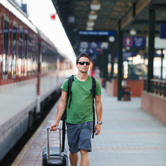 Just arrived: handsome young man walking along a platform