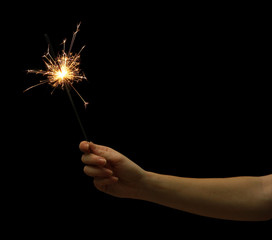 beautiful sparkler in woman hand on black background.