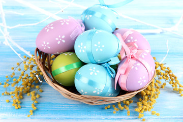Easter eggs in basket and mimosa flowers,
