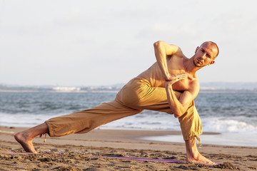 Wall Mural - Bare-chested man practicing yoga on mat at beach