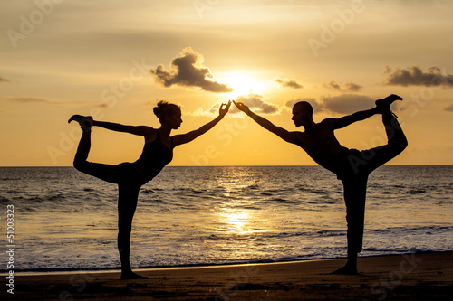 Wall mural Couple doing exercise yoga together stretching while sunset