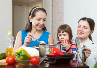 Mature woman and her daughter with baby cook lunch