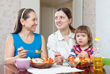 women with baby girl eats vegetables salad