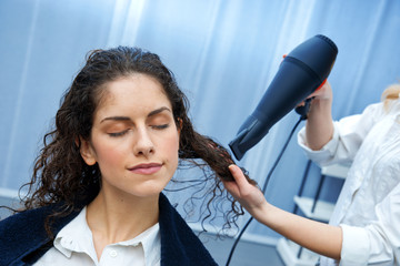 stylist drying woman hair in salon