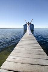 Fototapeta Joyful woman white dress on boardwalk