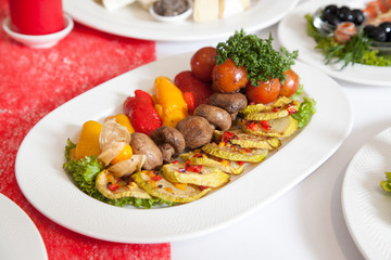 Plate on table with baked mushrooms and zucchini