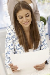 Pretty businesswoman looking at papers smiling