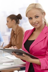 Businesswoman writing notes at meeting