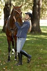 Female rider embracing horse