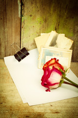 Red roses, white paper and old photos