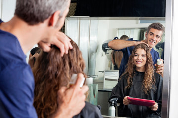 Hairdresser Setting Client's Hair While Looking At Mirror