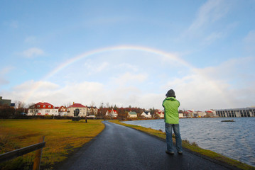 Man taking a picture of the rainbow, Reykjavik, Iceland