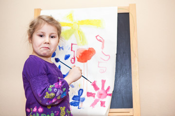 Girl`s emotions with painting a picture by brush and paints